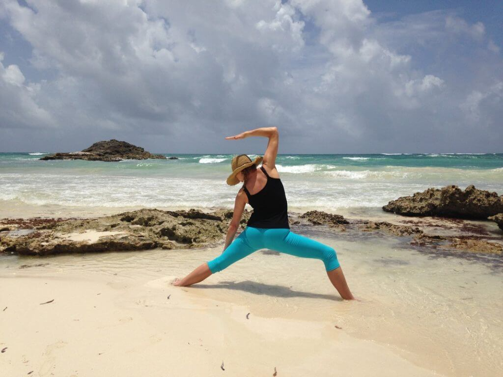 jenny rhodes yoga instructor doing yoga on beach